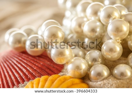 White pearl and seashells on sand background