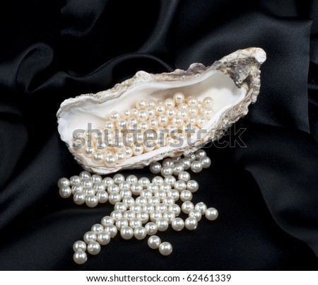White pearls scattered on a black background - stock photo