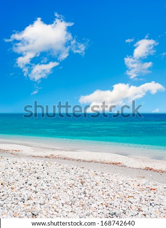 white pebbles by the sea on a cloudy day - stock photo