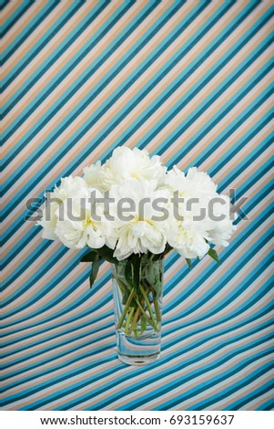 White peonies bouquet in a crystal vase on a blue and cyan diagonal striped background
