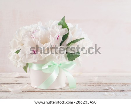 White peonies in vase on wood background, selective focus - stock photo