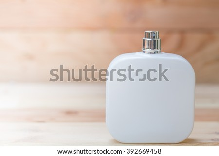 white perfume bottle on wood background.