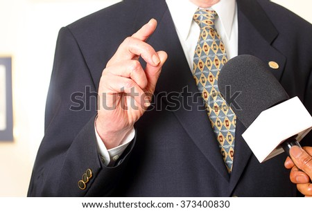 White person in business suit being interviewed by reporter of color - stock photo