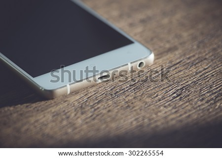 White phone on a wooden table. close-up - stock photo