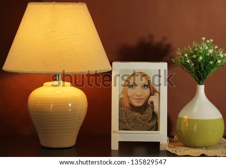 White photo frame and lamp on wooden table on brown wall background