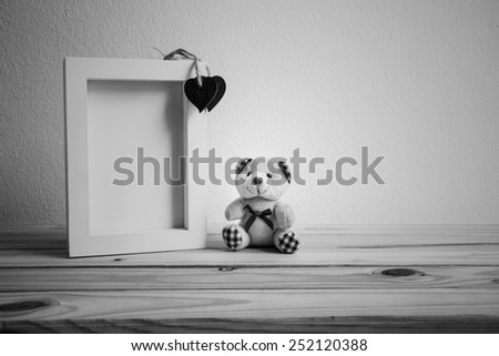 White photo frame and teddy bear on wooden table over grunge background, Valentine concept, black and white - stock photo