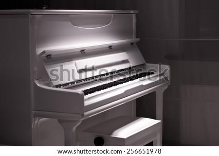 White piano in the dark. Piano chair - stock photo