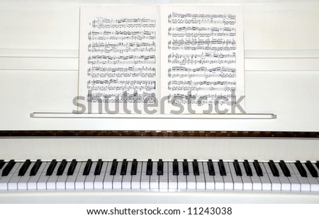 White piano with sheet music - stock photo