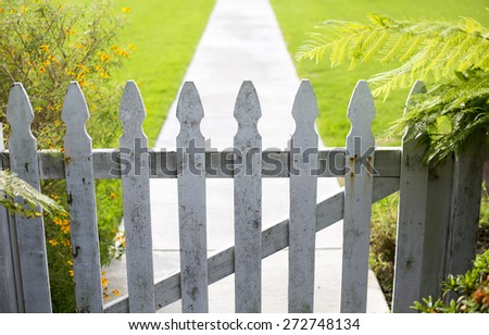 white picket fence and a walkway - stock photo
