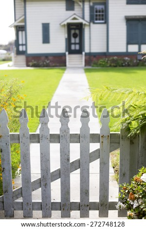 white picket fence and an entrance of a home - stock photo