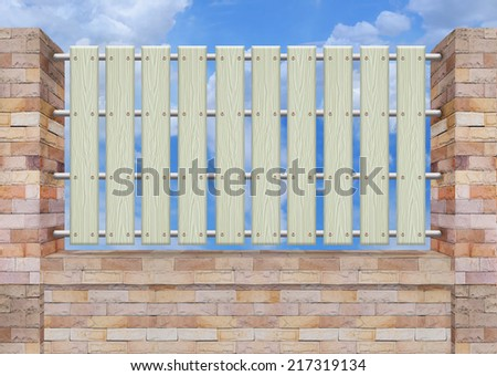 White picket fence, brick wall. - stock photo