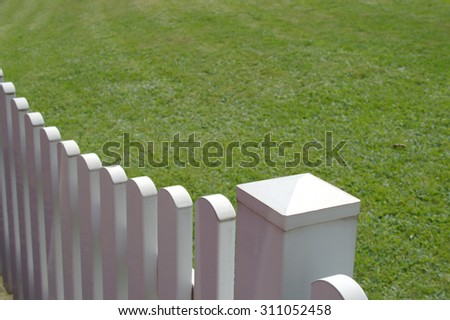 White picket-fence detail next to green grass as found in suburbs
