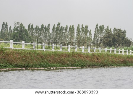 White picket fence separates the fields with canal water. - stock photo
