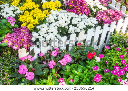 White picket fence surrounded by flowers in a front yard. Beautiful flower garden. - stock photo