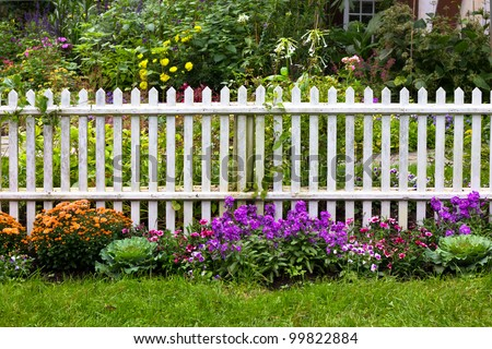 White picket fence with pretty flowers in a yard - stock photo