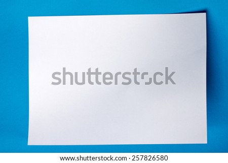 White piece of paper over a blue background. - stock photo
