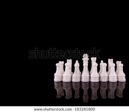 White pieces of stone made chess set over black background