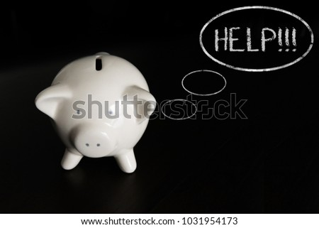 White piggy bank on dark wooden table with thought bubbles, thinking HELP