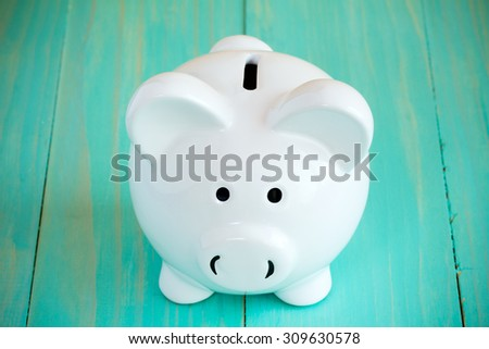 White piggy bank on the blue wooden background - stock photo