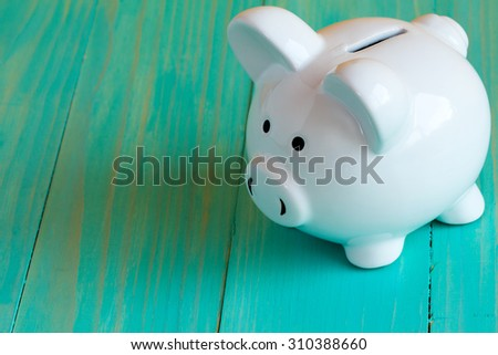 White piggy bank on the blue wooden surface - stock photo