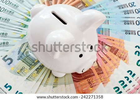 White piggy bank surrounded by Euro notes - stock photo