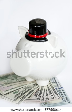 white piggy bank with bowler hat with money on a white background - stock photo