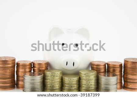 White Piggy bank With British Coins stacked in front, - stock photo