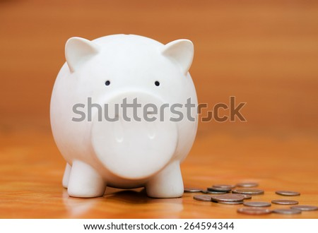 White piggy bank with coin wood background - stock photo