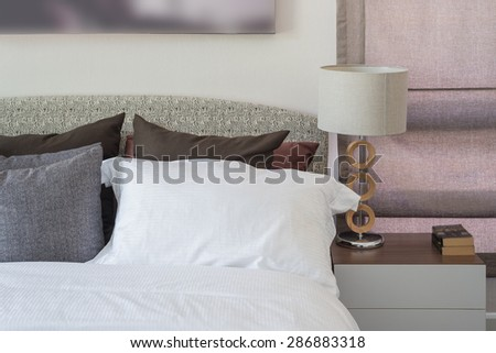 white pillow in modern bedroom with white lamp on table at home