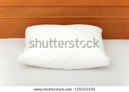 White pillow lying on bed