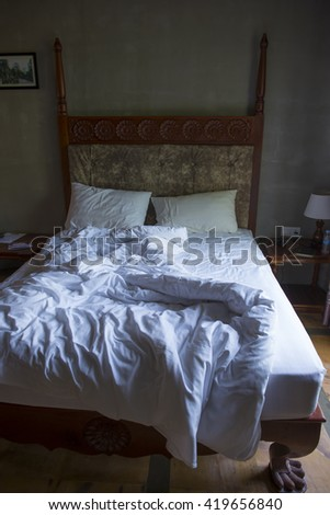 white pillow on bed and with wrinkle messy blanket in bedroom, from sleeping in a long night. - stock photo