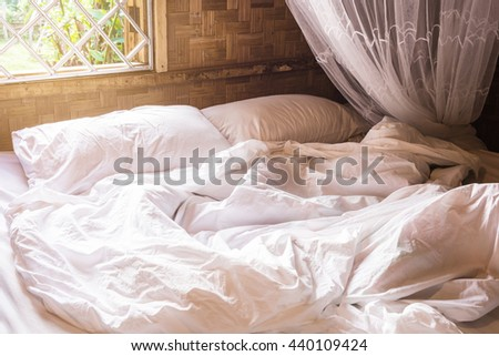 white pillow on bed and wrinkle messy blanket with mosquito nets in bedroom Thai lifestyles, from sleeping in a long night in winter.  - stock photo