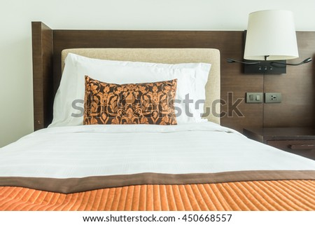 White pillow on bed decoration in bedroom interior with table light lamp