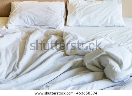 white pillows and wrinkle messy blanket on bed after waking up in the morning.