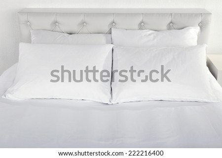 White pillows on bed in room - stock photo
