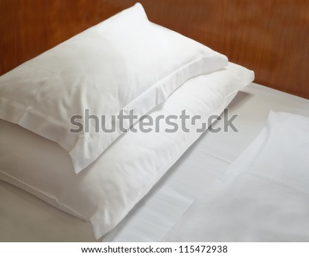 White pillows on wooden bed - stock photo