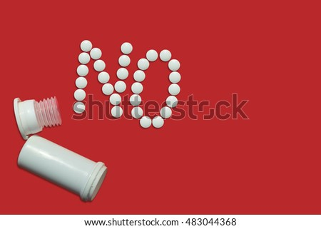"White pills and empty pill bottle forming a word ""NO"" on red background. Top view."