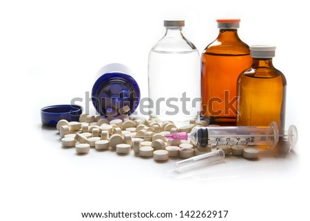White pills and medical equipment on white background.