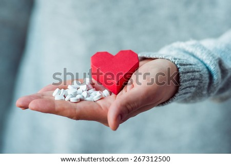 White pills and paper heart in hands. Medicine and health care concept - stock photo