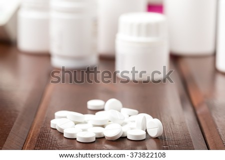 White pills and white plastic pill bottles - stock photo