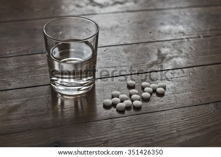 white pills lying next to a glass of water on a wooden table - stock photo
