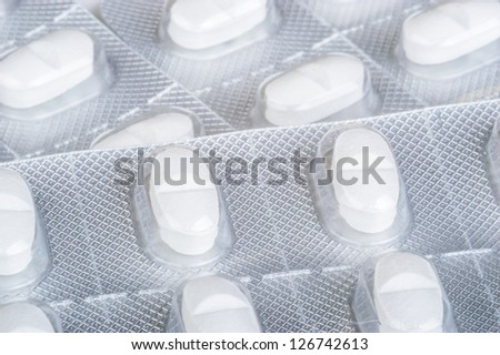 White pills of medication in protective packaging.