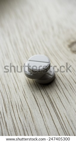 White pills on table. Pills spilling from container. Copy space. Slightly defocused and closeup shot. - stock photo