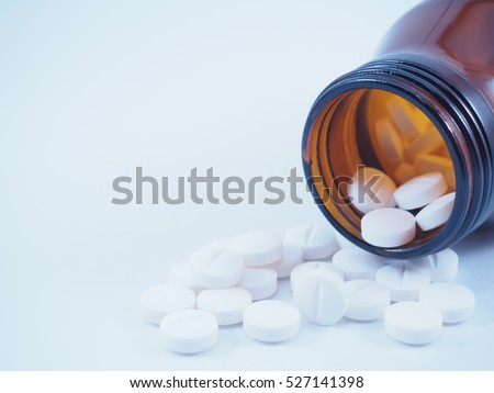 White pills or tablets spilling out of brown glass bottle on blue tone background. Medication concept. Copy space.