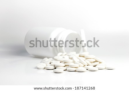 white pills out of pill bottle - stock photo