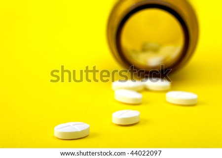 white pills out of the bottle on a yellow background
