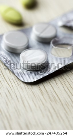 White pills strip and yellow pills on wooden table. Copy space. Slightly defocused and closeup shot. - stock photo