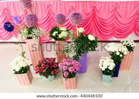 White, pink and violet bouquets stand in striped vases - stock photo