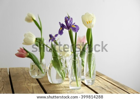White, pink tulips and purple iris in glass vases with water on wooden table, isolated on white