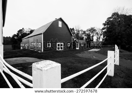 White pipe fence and American traditional barn. - stock photo